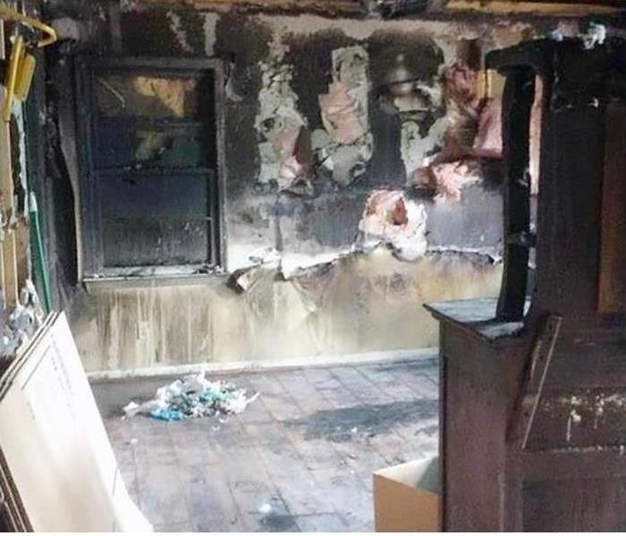 A family room in a home completely covered in smoke and soot damage from a fire