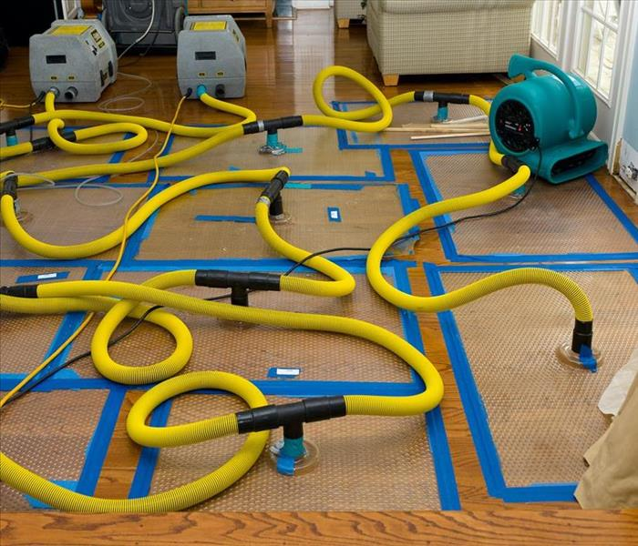Drying mats with yellow hoses connected to air movers