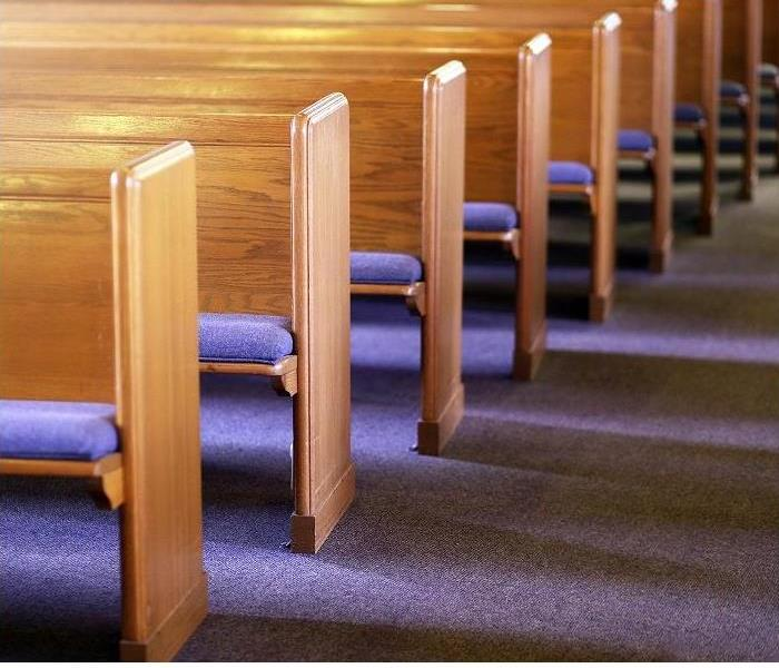 Row of empty church pews; carpeted floor