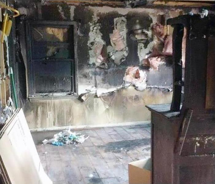 A room in a home completely covered in soot and smoke damage after a fire hit